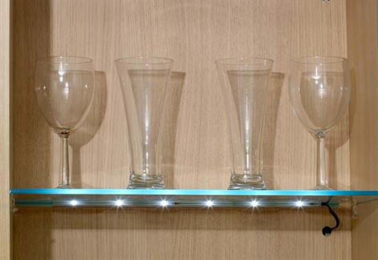 Illuminated glass shelf in a cupboard